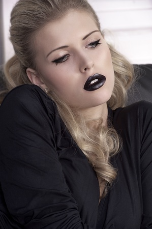 portrait of a pretty curly blonde girl wearing a black shirt and black lipstick photo