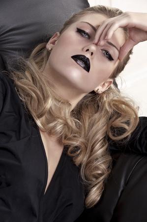 portrait shot of an elegant blonde curled girl wearing black lipstick and black eyeliner  photo