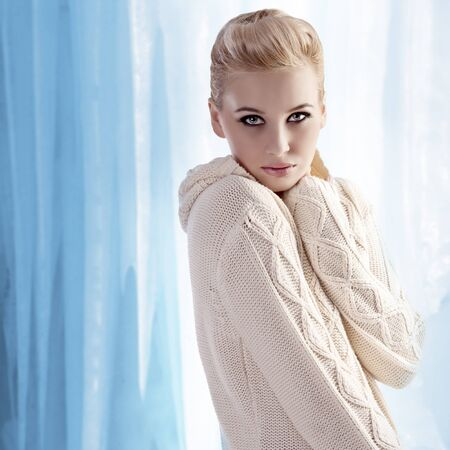 beautiful blonde with an up-do wearing a white and warm woolen sweater  photo