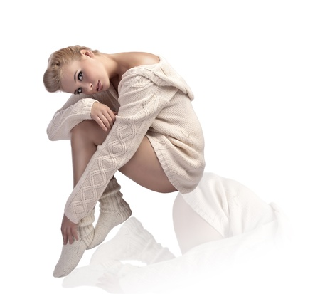 body shot of an attractive blonde sitting and wearing a woolen white jacket and comfy socks Stock Photo - 10914126