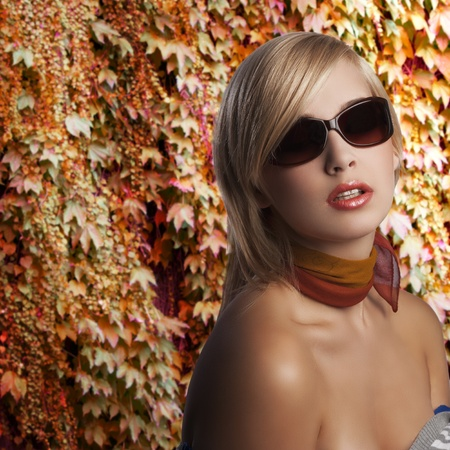 blond and beautiful young woman in a fashion portrait  sexy posing wearing sunglasses and an autumn scarf photo