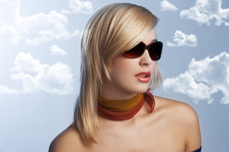 blond and beautiful young woman in a fashion portrait wearing sunglasses and an autumn scarf on grey background Stock Photo - 10917692