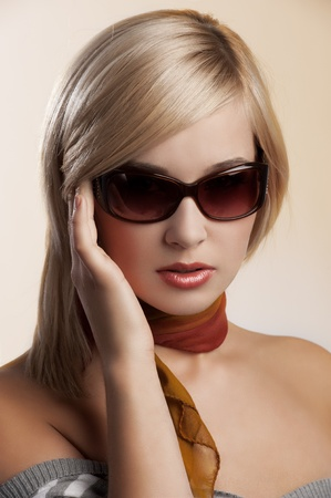 blond and beautiful young woman in a fashion portrait wearing sunglasses jumper and an autumn scarf photo
