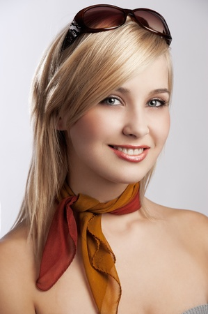 blond and beautiful young woman smiling in a fashion portrait wearing sunglasses and an autumn scarf photo