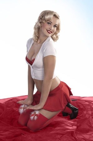 provocative women: blond and sexy girl with short skirt showing her red bra under white shirt in a pin up style wearing christmas stockings Stock Photo