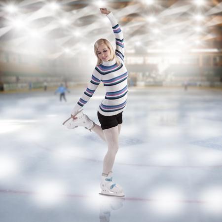 patinaje: chica linda y rubia con pantalones cortos y un suéter agradable hacer una figura de Patinaje sobre hielo