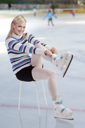 cute and blond girl with shorts and a nice sweater getting ready for ice skating  Stock Photo - 10917686