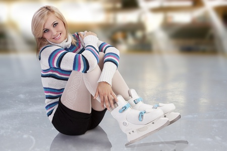 inline skater: cute and blond girl with shorts and a nice sweater sitting with ice skates on  Stock Photo