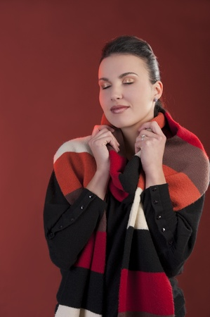 Autumn shot of a young pretty brunette wearing a dark sweater and a fall color long scarf  photo