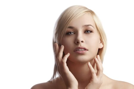 blond haired: beauty close up portrait of a young blond haired woman over white touching her cheeks  Stock Photo
