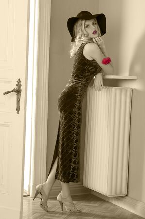 blond haired: fashion indoor shot of a beautiful blond curly haired girl with long elegant black dress and a black hat near old fashioned door looking at the camera