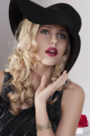 portrait of beautiful blond girl with curly hair and hat with black dress photo