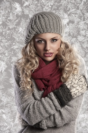 woman sweater: winter fashion shot of a beautiful girl with long curled blonde hair wearing a grey woolen cap, a grey sweater and warm gloves