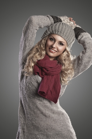 scarf: beautiful blonde curly girl in a winter fashion portrait wearing grey wool and a red scarf