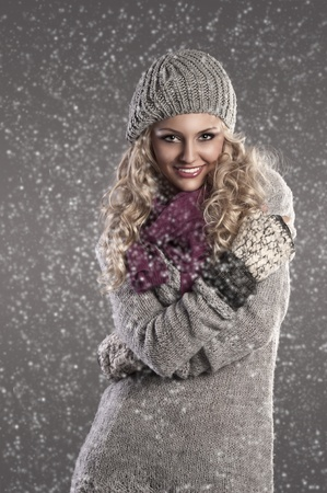winter fashion shot of a smiling attractive blonde wearing a wool cap, a grey wool sweater, gloves and a purple scarf