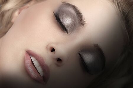 beauty close up portrait of a blonde beautiful girl closing her eyes and smokey eyes make up Stock Photo - 11032222