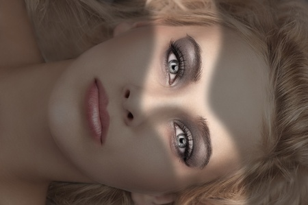 beauty close up portrait of a laying blonde with grey eyes, smokey eyes make up and soft pink glossy lips Stock Photo