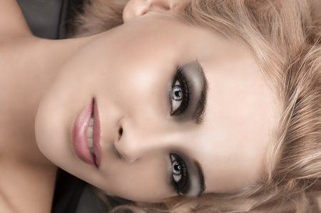 beauty close up of a gorgeous blonde girl with sophisticated smokey eyes make up photo
