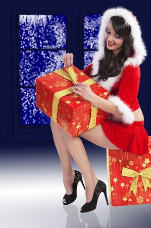 Sexy model in a red christmas dress with short skirt and hood with white fur and a big gift box sitting in front of a snowy window photo
