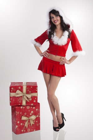 Sexy model in a red christmas dress with short skirt and hood with white fur and 2 big gift boxes over grey-white background photo