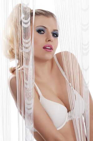 sexy bride: sexy blond young woman wering a lingerie bra playing behind with curtain with beautiful pose towards the camera on white background