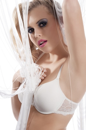sexy bride: sexy blond young woman wearing a lingerie bra playing behind with curtain with sexy pose while looking at the camera on white background