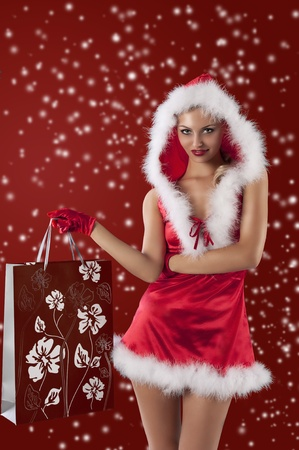 short gloves: christmas glamour shot of a sexy blonde dresses as female santa claus with a short red dress and red gloves Stock Photo