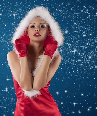 young and sexy woman in red santa claus dress with hood and white fur and gloves  photo