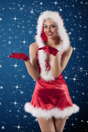 sexy shot of a female santa claus dressed with a red mini dress, hood and gloves smiling photo