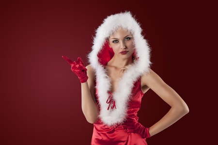 beautiful and sexy girl posing in a red and very short christmas outfit with white feathers photo