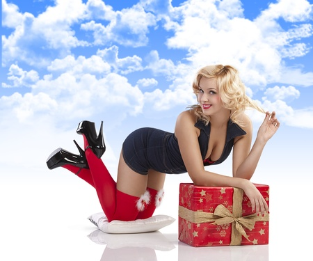 very attractive and sexy blond pin up with red christmas stocking and a big present box laying on the floor with sexy pose against white background photo