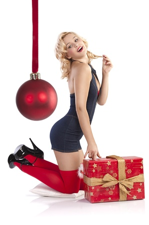 very attractive and sexy blond pin up with red christmas stocking and a big present box sitting in knees and posing on the floor against white background photo