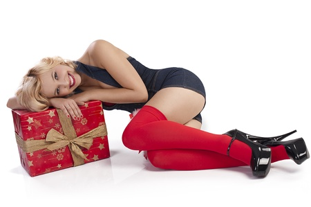 very attractive and sexy blond pin up with red christmas stocking and a big present box laying on the floor Standard-Bild