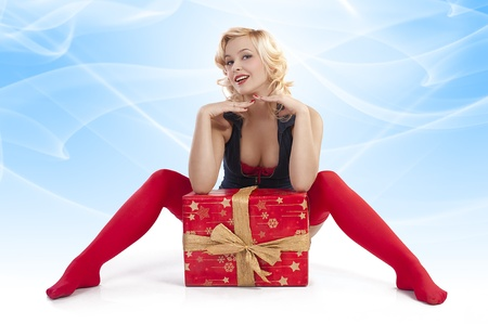very attractive and sexy blond pin up with red christmas stocking and a big present box posing while on the floor against white background Stock Photo
