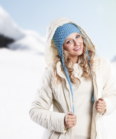 winter shot of a young pretty woman wearing a light blue hat and white sweater and scarf over white photo