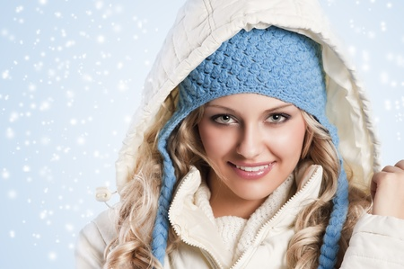 winter shot of a young pretty woman wearing a light blue hat and white sweater and scarf over white Standard-Bild
