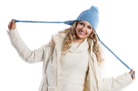 winter shot of a young pretty woman wearing a light blue hat and white sweater and scarf over white, she's playing with the hat's braids Stock Photo - 11086061