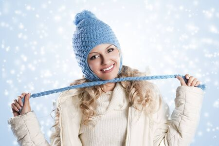 winter shot of a young pretty woman wearing a light blue hat and white sweater and scarf over white, in this shoot ses making a node with the pigtails of the hat. photo