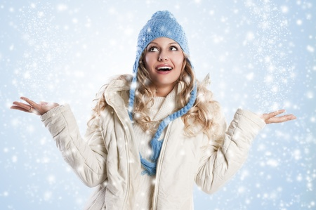 winter shot of a young pretty woman wearing a light blue hat and white sweater and scarf over white, shes looking up with an expression of surprise photo