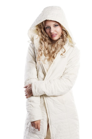 Blond curly haired woman wearing a white winter jacket with a hood making face and enjoing over white, her right hand takes left elbow photo