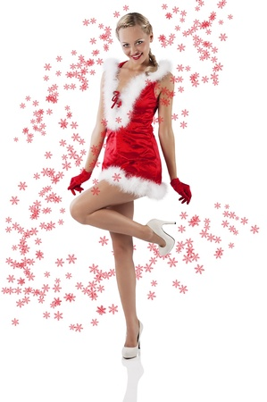 young and sexy woman in red santa claus dress with hood and white fur and gloves standing on one foot photo