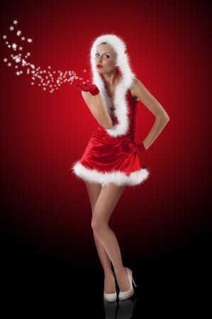 jonge en sexy vrouw in rode santa claus jurk met capuchon en witte vacht en handschoenen waait kerstcadeaus