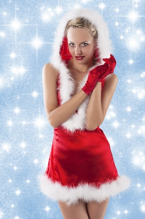 young and sexy woman in red santa claus dress with hood and white fur and gloves clapping hands photo