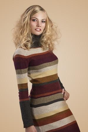 maglioni: moda autunno colpo di una bellezza naturale bionda indossa un abito a righe di lana