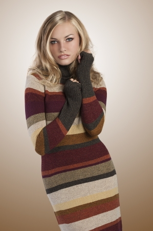 fashion shot of a blonde autumn girl posing in a long woolen striped dress photo
