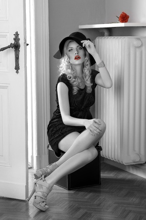erotic dress: fashion shot of a pretty girl in a black dress wearing a huge hat and sitting in an old fashion room