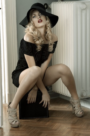 hat nude: fashion shot of a beautiful and sensual young lady posing wearing a huge hat and an elegant black dress