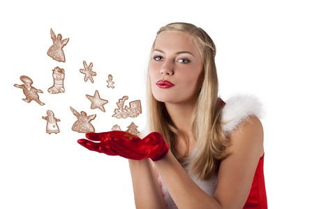 pretty and sensual blond girl in santa claus red dress posing a smiling with a nice hairstyle blowing cookies photo