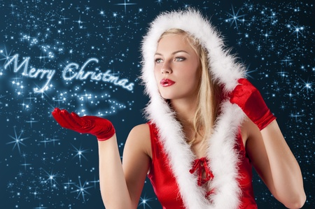 pretty and sensual blond girl in santa claus red dress posing a smiling with a nice hairstyle blowing from hand... photo
