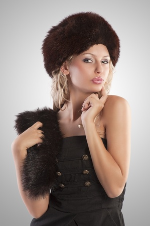 very beautiful fashion woman wearing an elegant black dress with boot and winter fur hat with stole on grey spotlight background photo